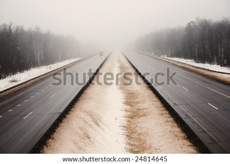 Snowy empty highway in the dark foggy forest