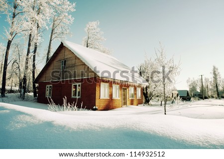 Snowy hills in Russian countryside in morning, red wooden house windows turned to east