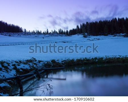 Snowy landscape with forest and little lake