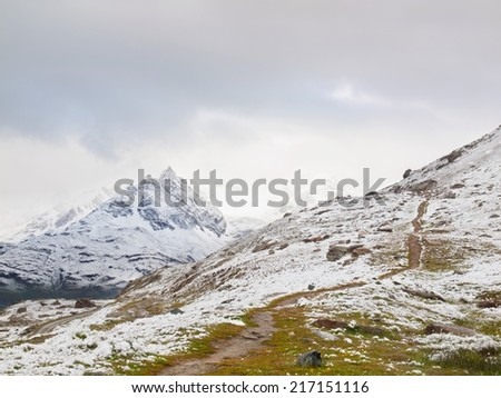 Snowy landscape with gravelly road. Misty sharp peaks of  high mountains in background.