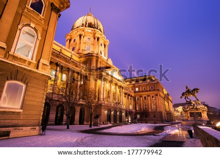 Snowy main facade of the historic Royal Palace - Buda Castle in Budapest under a purplish blue sky at nightfall - Hungary at night - stock photo