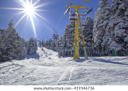 Snowy Mountain And Ski Lift.Skiers moving up to the mountain by ski lift in the sunny day. - stock photo