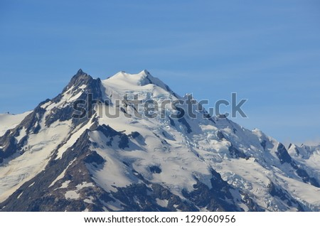 Snowy mountain peak with glaciers - stock photo