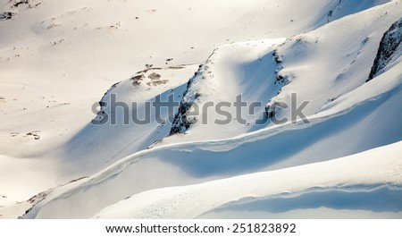 snowy mountain peaks against the blue sky - stock photo
