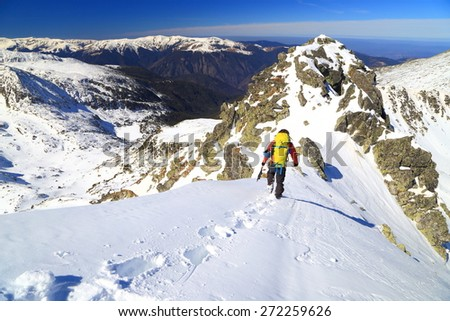Snowy mountain ridge with distant mountaineer in sunny winter day - stock photo