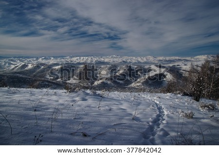 Snowy mountain slope with a path in the foreground and mountains in the background. Altai Mountains, Siberia, Russia - stock photo