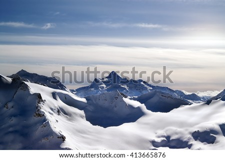 Snowy mountains in evening. View from ski slope mt. Elbrus, Caucasus Mountains. - stock photo