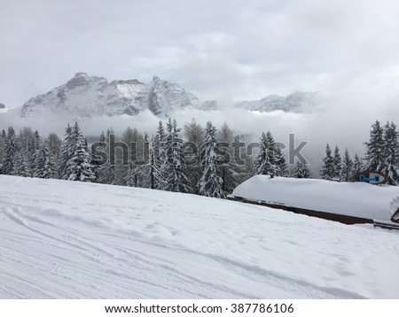 Snowy mountains in the clouds in Italian Alps. - stock photo