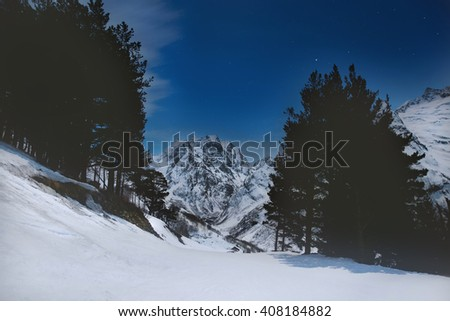 Snowy mountains in the moonlight and the stars. Night winter mountain landscape.