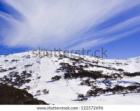 snowy mountains ski resort and snowboarding chairlift up to mountain top valley landscape with cloudy blue sky over peaks - stock photo