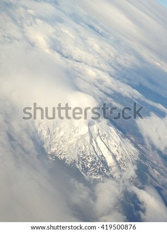 Snowy mountaintop and clouds - stock photo