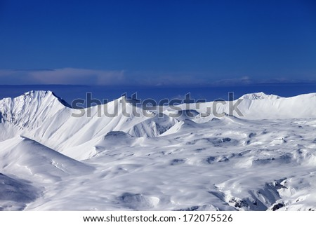 Snowy plateau at sunny day and blue sky. Caucasus Mountains, Georgia, view from ski resort Gudauri. - stock photo