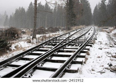 snowy railway track in a winter forest - stock photo