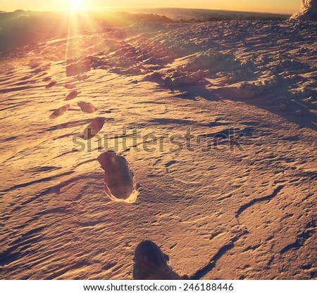 Snowy ridges dressed in a blanket of snow and ice, panorama alpine meadows in the cold like a frozen ocean during a storm. Travelling and climbing gives an unforgettable experience at Christmas  - stock photo