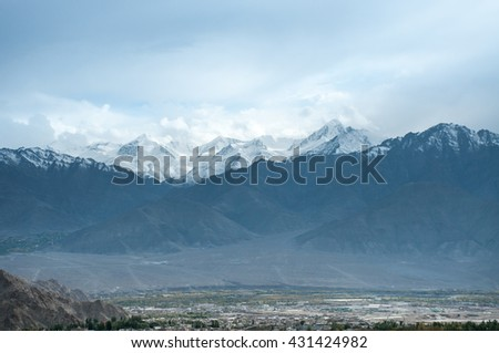 Snowy rock mountain and little city in Leh, Ladakh, India.