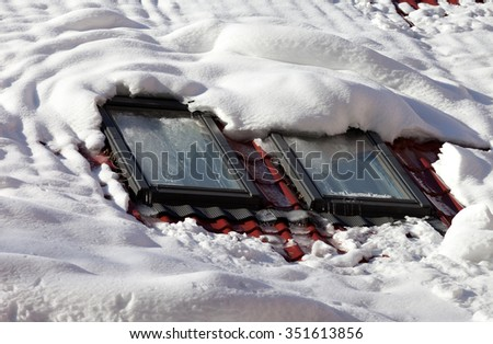 Snowy roof with icy windows at nice sun day - stock photo