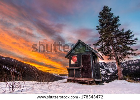 Snowy shack with tree in a ski resort at sunset - stock photo