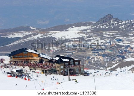 Snowy ski slopes of Pradollano ski resort in the Sierra Nevada mountains in Spain with people skiing and snowboarding near a restaurant - stock photo