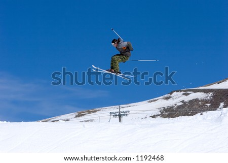 Snowy ski slopes of Pradollano ski resort in the Sierra Nevada mountains in Spain with skier making a big jump - stock photo