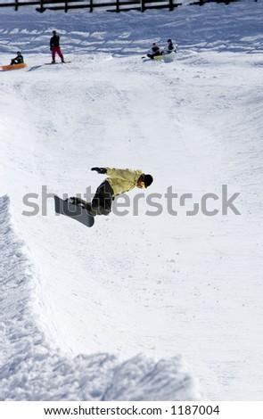 Snowy ski slopes of Pradollano ski resort in the Sierra Nevada mountains in Spain with snowboarder in half pipe - stock photo