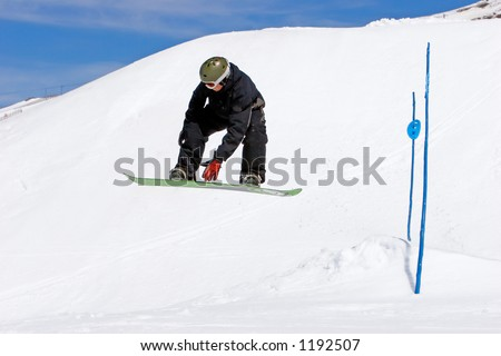 Snowy ski slopes of Pradollano ski resort in the Sierra Nevada mountains in Spain with snowboarder making a jump - stock photo