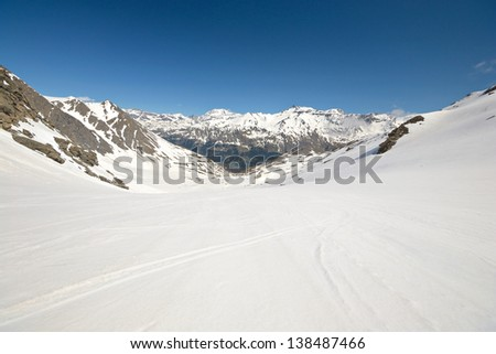 Snowy slope with melting grooves in scenic high mountain background and sunny spring day. Location: italian french Alps. - stock photo