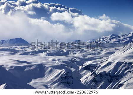 Snowy sunlight plateau and blue sky with clouds. Caucasus Mountains, Georgia, view from ski resort Gudauri. - stock photo