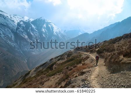 Snowy Tibetan mountains with hiking man - stock photo