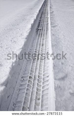 Snowy tire track from a car going through deep snow.