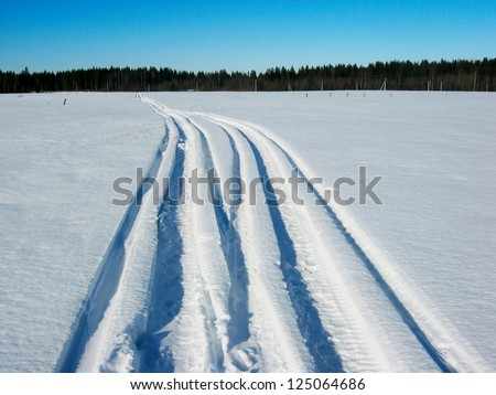 Snowy track.  Snowmobile trail from left in a snowy field - stock photo