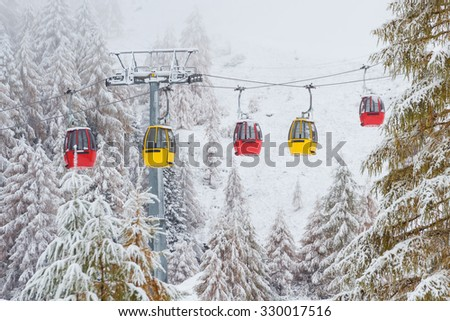 Snowy trees and colorful rail car Dolomites Italy - stock photo