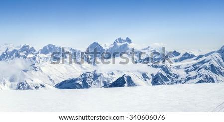 Snowy winter Greater Caucasus mountains (Ushba, Kogutai and other) at sunny day. Panorama view from ski slope Elbrus, Kabardino-Balkaria, Russia - stock photo