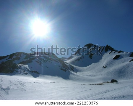 Snowy winter landscape in the mountains on a clear, sunny day - stock photo