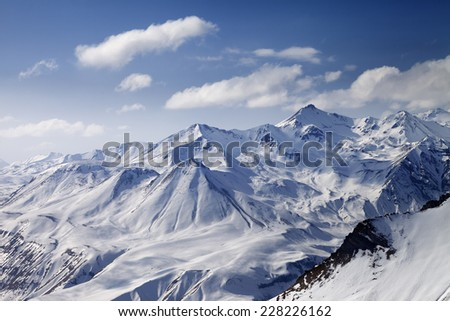 Snowy winter mountains in sun day. Caucasus Mountains, Georgia, from ski resort Gudauri. - stock photo