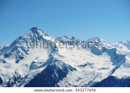 Snowy winter mountains. View on skiing slopes at ski resort at Alps on a sunny day with blue sky