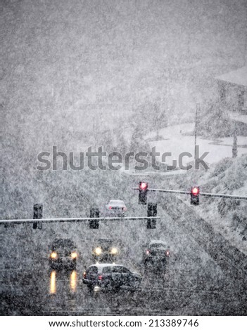 Snowy winter road with cars driving on roadway in snow storm - stock photo