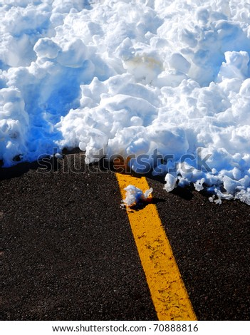 Snowy winter road with yellow line and snow drift - stock photo