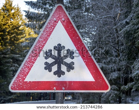 snowy winter warning sign on a road, car with lights on driving by - stock photo