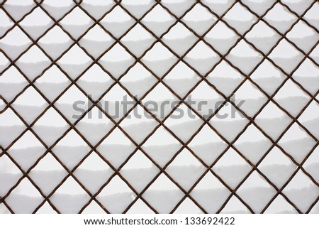 Snowy wires of a chain link fence for backgrounds