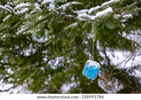 Snowy wrapped blue Christmas present hanging on a fir-tree - stock photo