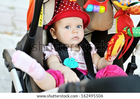 so cute baby sitting in the stroller - stock photo
