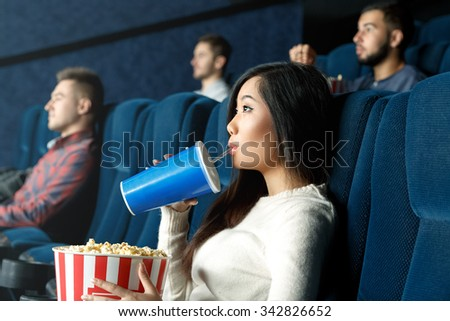 So entertained. Portrait of a young Asian woman drinking her beverage watching movie attentively at the local cinema - stock photo