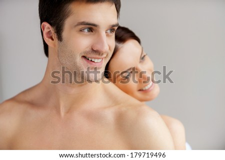 So good to be together. Cheerful young loving couple standing back to back and smiling - stock photo
