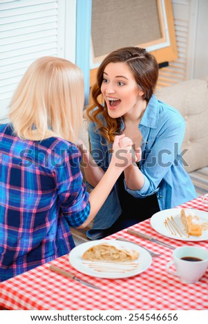 So happy for you. Top view of two young beautiful female friends sitting in cafe and holding hands while discussing some exciting news  - stock photo