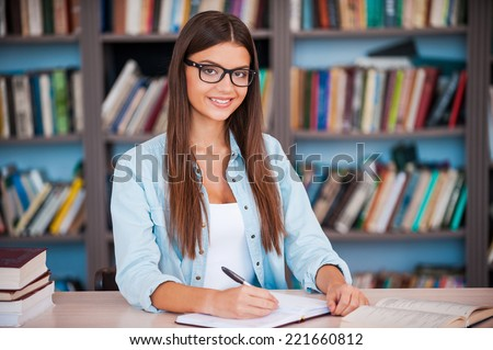 So happy to be a student! Beautiful young woman writing something in her note pad and looking at camera while sitting at the desk in the library - stock photo