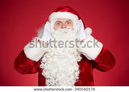 So much to do so little time. Horizontal portrait of worried Santa holding his hand in his hands looking to the camera with his eyes wide open - stock photo