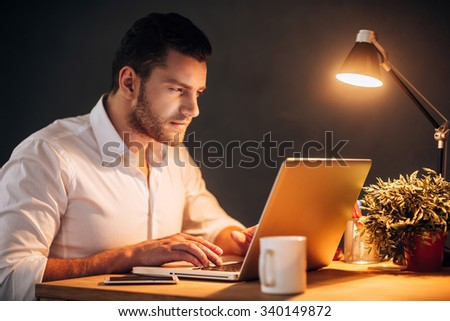 So much work today! Confident young man working on his laptop while sitting at his working place at night time - stock photo