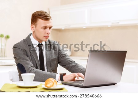So serious. Serious businessman in suit working on computer in kitchen.