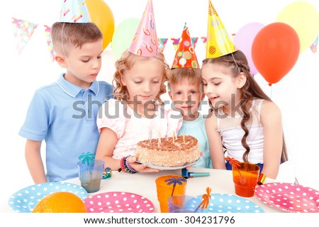 So tasty. Group of little cute smiling children curiously looking at cake during birthday party