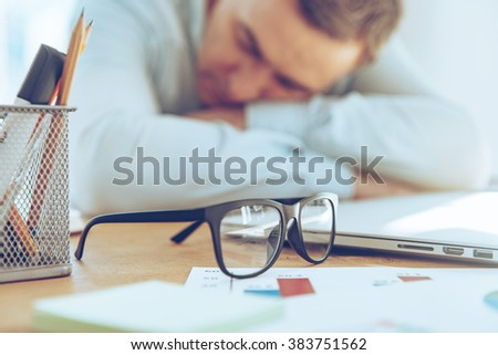 So tired. Close-up of mature man sleeping at his working place  - stock photo
